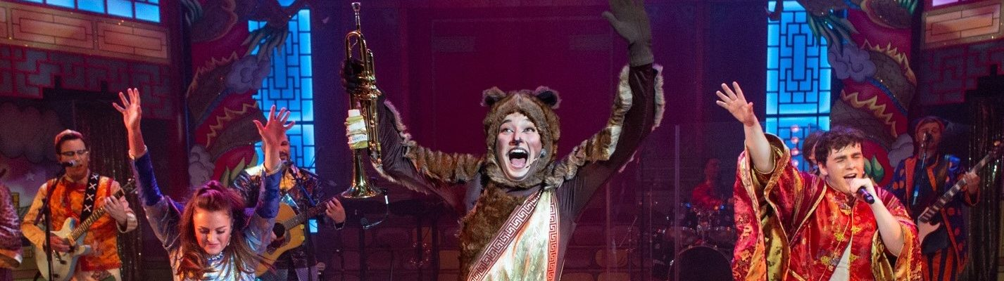 A photograph from the 2019 pantomime, Aladdin, in which there are three main people in the photographs. The middle figure, closest to the camera, is Cuddles the Monkey, arms up in the air and right leg stuck out (a pose copied by the two figures behind). In Cuddles' right hand is a trumpet. Princess Firecracker, in a blue outfit, is on the left of the image and Aladdin is on the right, holding a microphone to his face as he sings and jumps. Behind them, the rest of the cast can be seen playing various musical instruments.
