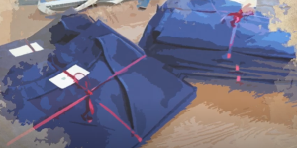 The image shows a still from the video, depicting deep blue hospital scrubs tied neatly in red ribbon, folded on a table. The image has the effect of looking like it's been painted in watercolour.