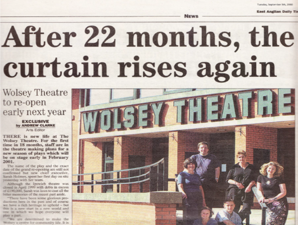 An image of a newspaper article from the East Anglian Daily Times, dated Tuesday 5th September 2000, with the title 'After 22 months, the curtain rises again.' Beneath the heading is an image of the front of the theatre, 'Wolsey Theatre' spelled out in big block-style letters above the door. At the steps out the front, six people, including our Chief Executive Sarah Holmes, stand together, smiling for the camera on their first day at work.