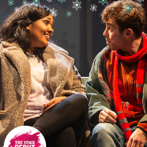 Robyn (left) and Dougal (right) sit on a park bench smiling at each other, dressed in warm winter coats and scarves. The signs of New York City are vaguely visible in the background. Snowflakes border the top of the image and in the bottom left corner is a white circle containing the logo for The Stage Debut Awards - white text reading 'The Stage Debut Awards in association with Access Entertainment' over the top of bright pink brushstrokes.