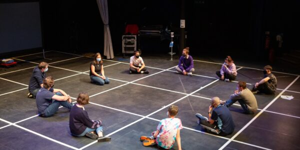 The photograph shows a group of young people sitting in a circle on the New Wolsey stage. They are in the middle of a workshop, all wearing masks and socially distanced.