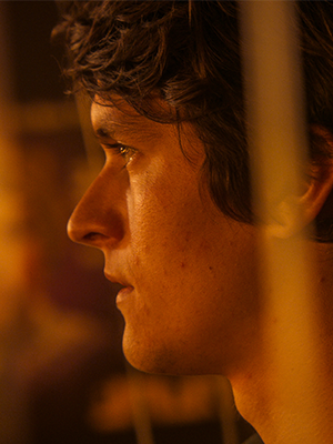 The photograph, bathed in an amber light, shows the profile of Fionn Whitehead as Dorian Gray, looking off-camera to the left. His face wears a serious expression.