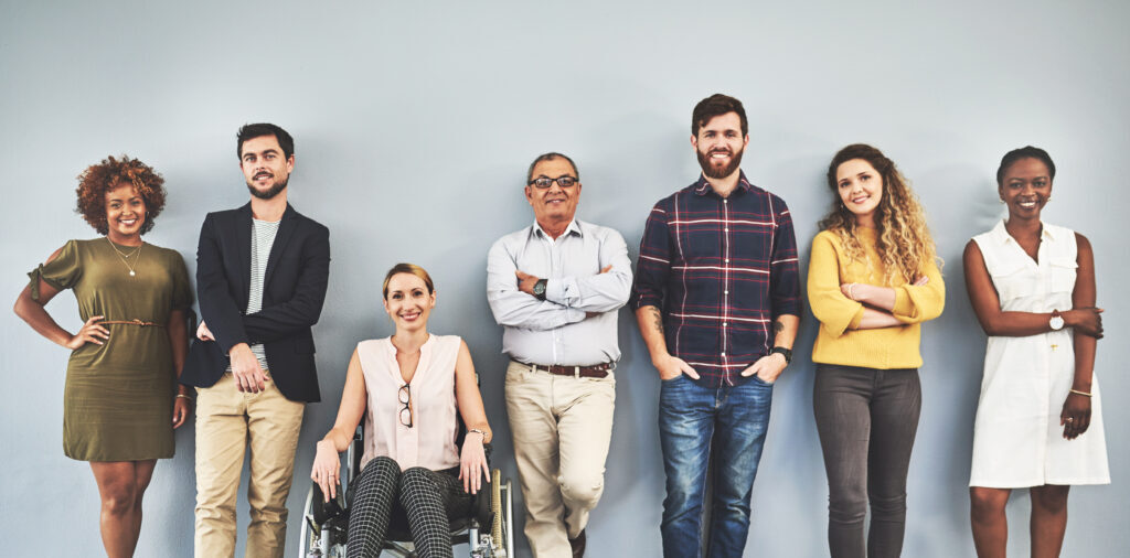 The image shows a diverse group of people, smiling in front of a light grey wall.