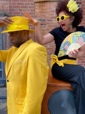A man in a yellow suit with matching top hat stands in the left of the photograph, holding crossly onto his hat. A woman sits on a large speaker behind him, wearing dark clothing with yellow accessories. She is gleefully trying to pinch his hat from his head.