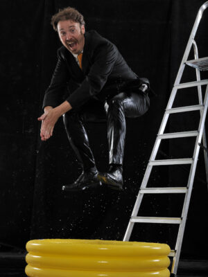 The photo shows a man comedically jumping off a ladder into a small yellow paddling pool. He is grinning at the camera in mid-air and has his knees tucked up to his chest and hands together pointing down as if diving.
