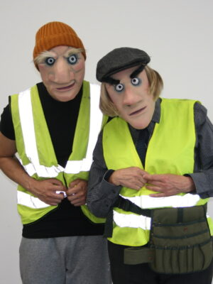 The image shows two men wearing high visibility jackets over their dark clothing and masks that exaggerate their facial features, particularly their eyes and noses. One man wears a beanie hat and the other wears a flat cap. Both men have their hands held together in front of their stomachs and they are tucked next to each other as if for protection. The background is plain white.