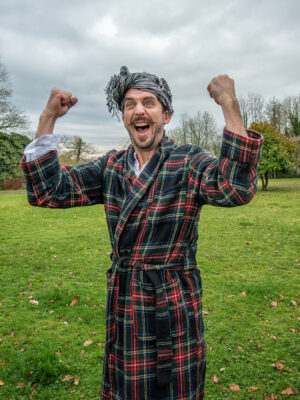 Murray Lachlan Young stands outside in a dressing gown, his arms held up and pulling a face.