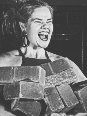 The black and white image shows a Strong Woman holding a pile of bricks and grinning at the camera.