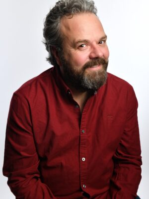 Hal Cruttenden smiles at the camera, wearing a red shirt against a white background.