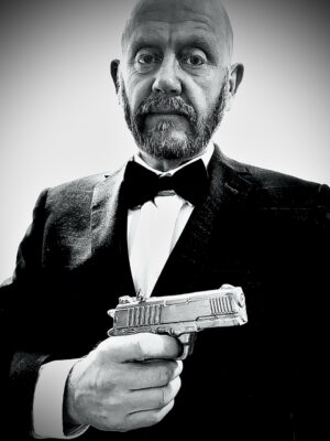 A black and white photo of John Smith wearing a suit and bow tie, holding a pistol to his chest, pointing it off-camera to the right.